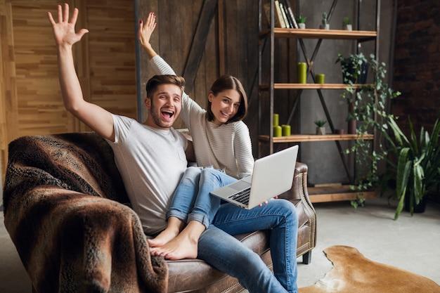 Giovane coppia sorridente seduto sul divano a casa in abito casual, amore e romanticismo, donna e uomo che si abbracciano, indossa jeans, trascorrono momenti di relax insieme, tenendo il laptop, felice emotivo