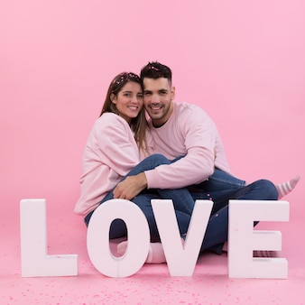 Young smiling couple sitting near big love sign and confetti
