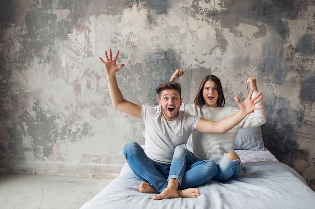 カジュアルな服装で自宅のベッドに座っている若い笑顔のカップル、男と女が一緒に楽しんで、クレイジーな肯定的な感情、幸せ、手をつないで