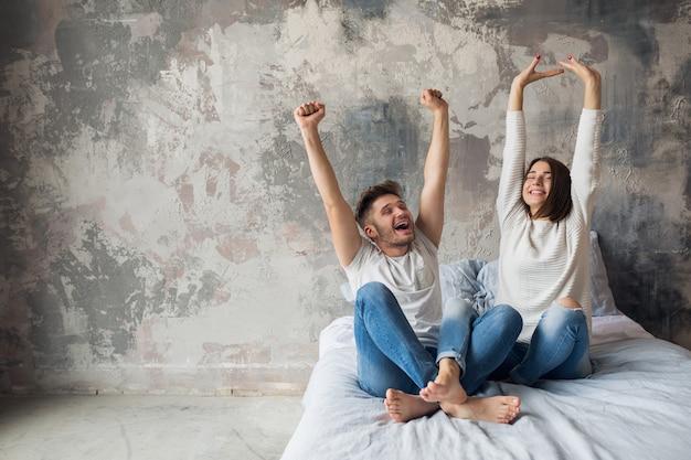 Молодая улыбающаяся пара сидит на кровати дома в повседневной одежде, мужчина и женщина веселятся вместе, сумасшедшие положительные эмоции, счастливы, держась за руки