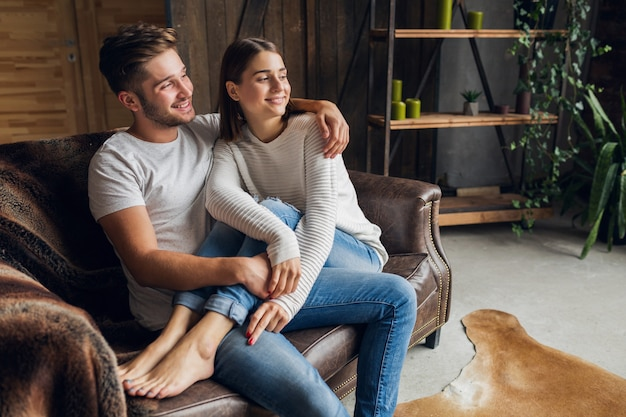 Молодая улыбающаяся пара, сидящая на диване дома в повседневной одежде, любовь и романтика, женщина и мужчина, обнимаются, в джинсах, вместе проводят время, расслабляясь