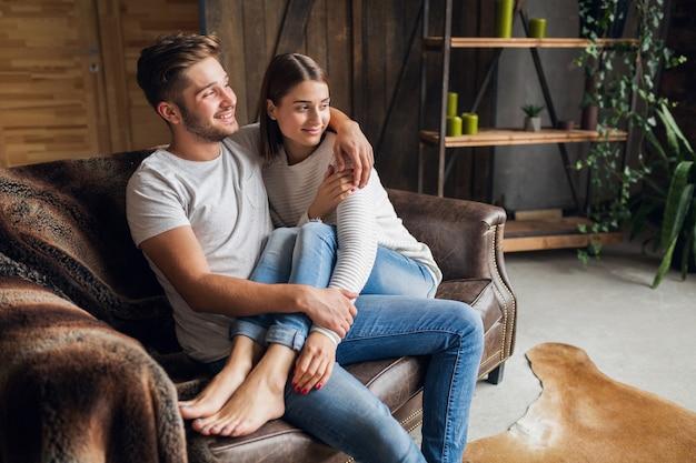 カジュアルな服装で自宅のソファに座っている若い笑顔カップル