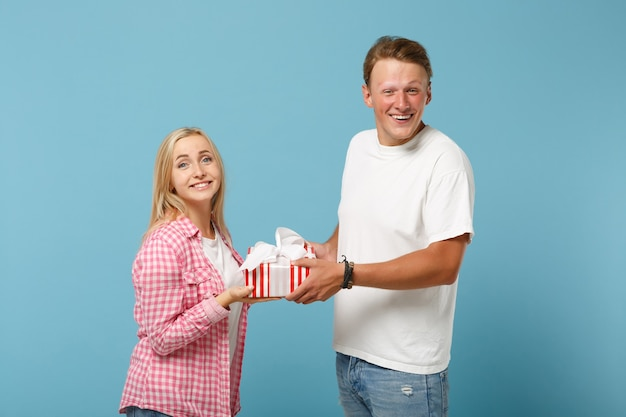 Young smiling couple two friends guy and woman in white pink t-shirts posing