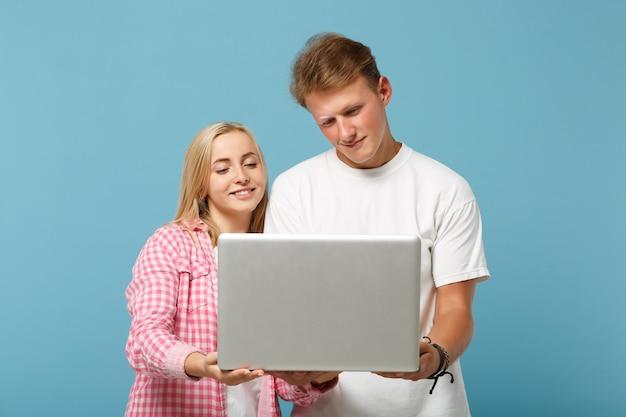 白いピンクの空の空白のtシャツのポーズで若い笑顔のカップル2人の友人の男性と女性