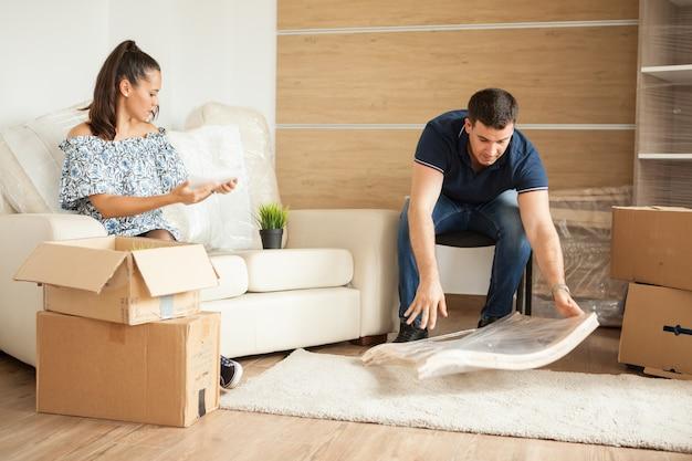 젊은 미소 커플이 소파에 함께 앉아 골판지 상자를 풀고 있습니다. 거실에 앉아.