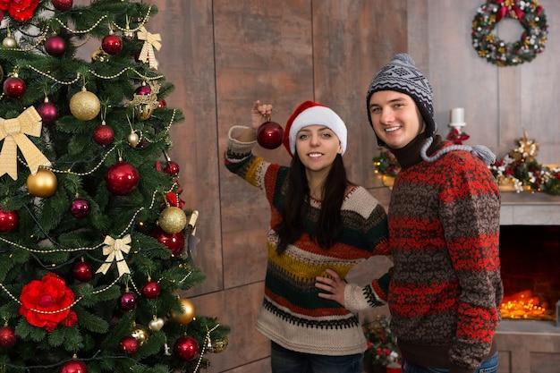 面白い帽子をかぶって、リビングルームの大きなクリスマスツリーに飾りや装飾品をぶら下げてクリスマスを飾る若い笑顔のカップル