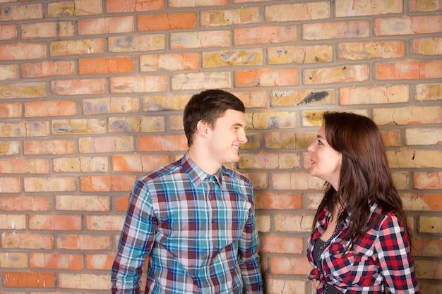 格子縞のシャツを着て向かい合ってレンガの壁の前に立っている若い笑顔のカップル