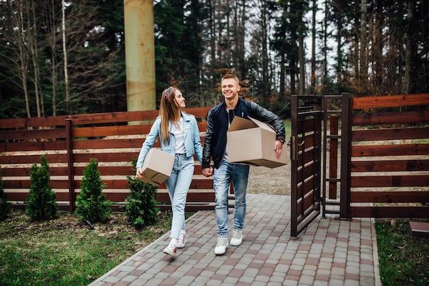 Молодая пара улыбается с коробками в день переезда. счастливые домовладельцы или арендаторы только что переехали в современный дом с террасой.