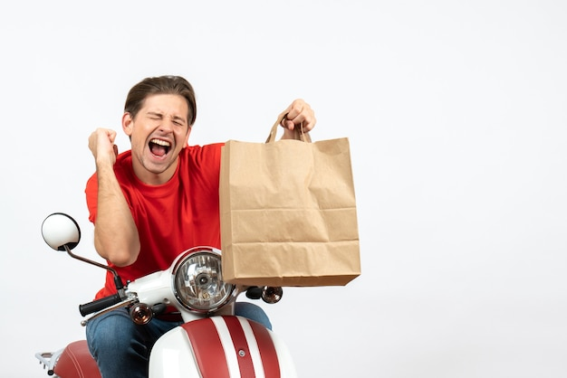 Молодой улыбающийся курьер в красной форме сидит на скутере с бумажным пакетом, наслаждаясь своим успехом на белой стене