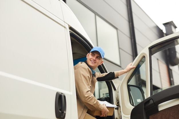 Young smiling courier holding package while sitting in the van he delivering parcels