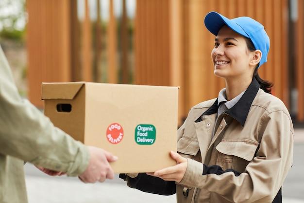 Молодой улыбающийся курьер в униформе доставляет посылку мужчине на открытом воздухе