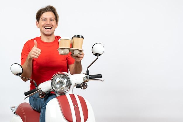 スクーターに座って注文を保持している赤い制服を着た若い笑顔の宅配便の男