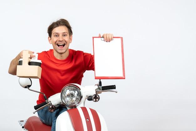 Giovane uomo sorridente del corriere in uniforme rossa che si siede sul motorino che tiene ordini e documenti sulla parete gialla