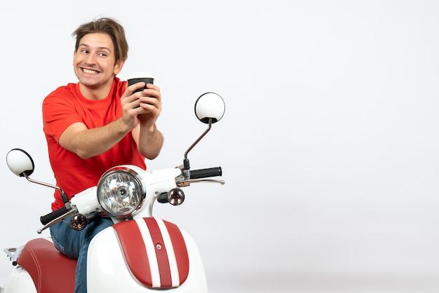 Giovane uomo sorridente del corriere in uniforme rossa che si siede sul motorino che tiene la tazza di carta sulla parete gialla