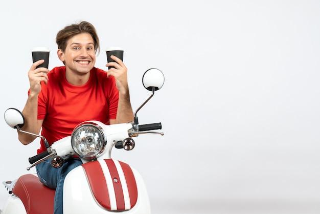 Giovane uomo sorridente del corriere in uniforme rossa che si siede sul motorino che tiene i bicchieri di carta sulla parete gialla
