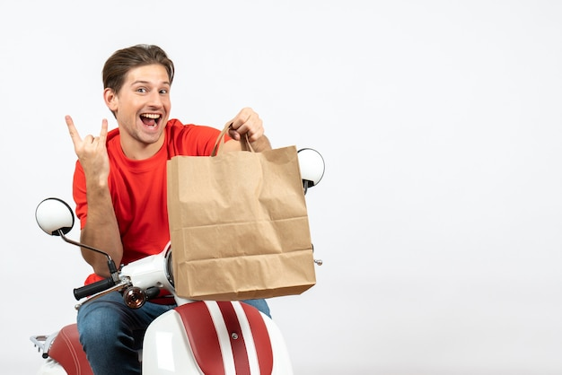 Young smiling crazy emotional courier guy in red uniform sitting on scooter holding paper bag on white wall