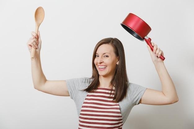 Молодая улыбающаяся шальная домохозяйка в полосатом фартуке, серой изолированной футболке. красивая веселая домработница, держащая красный пустой сотейник на голове деревянной ложкой