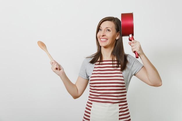 Giovane casalinga pazza sorridente in grembiule a strisce, maglietta grigia isolata. bella donna governante divertente che tiene una casseruola vuota rossa alla testa del cucchiaio di legno