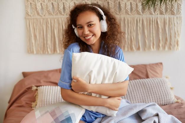 Giovane sorridente ragazza afroamericana riccia ubicazione sul letto, abbracciando un cuscino, ascoltando la canzone preferita in cuffia, ampiamente sorridente.