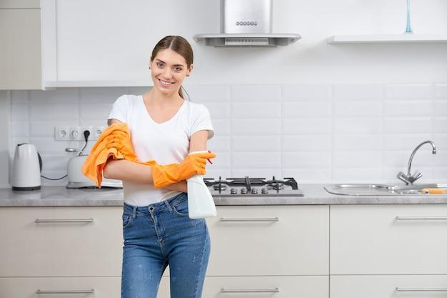 Молодая улыбающаяся милая женщина, убирающая кухню