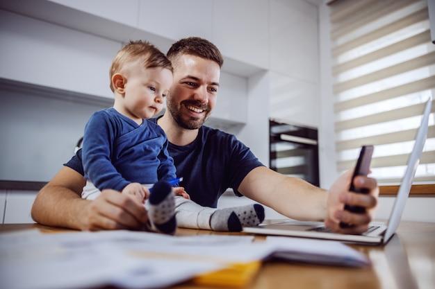Молодой улыбающийся папа, делающий селфи со своим любимым единственным сыном, сидящим за обеденным столом. концепция семейных ценностей.