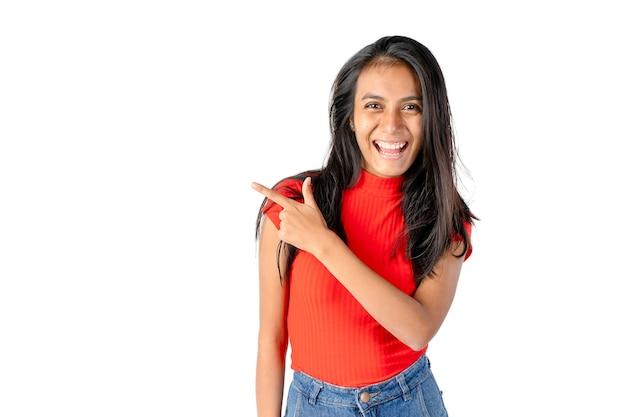 순수한 흰색 배경에 그녀의 오른쪽을 가리키는 젊은 웃는 검은 머리 라틴 여자.