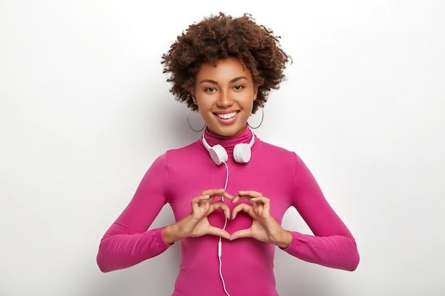 アフロヘアカットで若い笑顔の暗い肌の女性は、心臓のジェスチャーを行い、誰かに愛を示しています