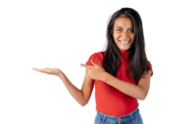 오른손으로 그녀의 옆구리를 확장하고 순수한 흰색 배경에 그것을 가리키는 왼손을 가진 젊은 웃는 검은 머리 라틴 여자.