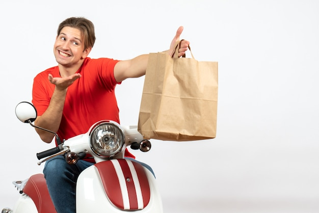 Young smiling delivery guy in red uniform sitting on scooter giving paper bag to someone on yellow wall