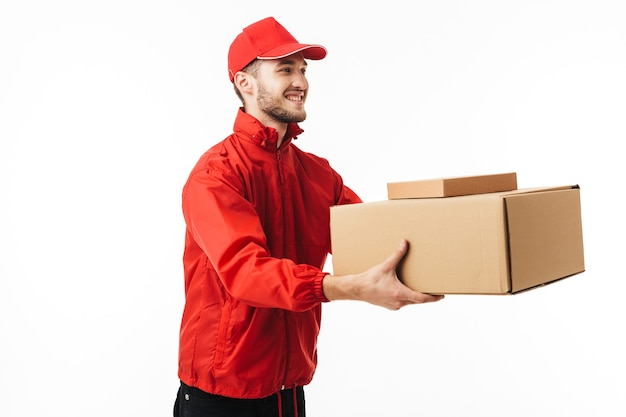Young smiling delivery man in red cap and jacket giving boxes to customer happily