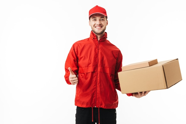 Young smiling delivery man in red cap and jacket holding boxes in hand happily showing thumb up gesture while