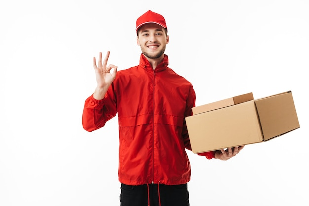 Young smiling delivery man in red cap and jacket holding boxes in hand joyfully showing ok gesture
