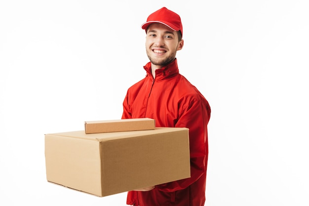 Young smiling delivery man in red cap and jacket holding boxes in hands happily