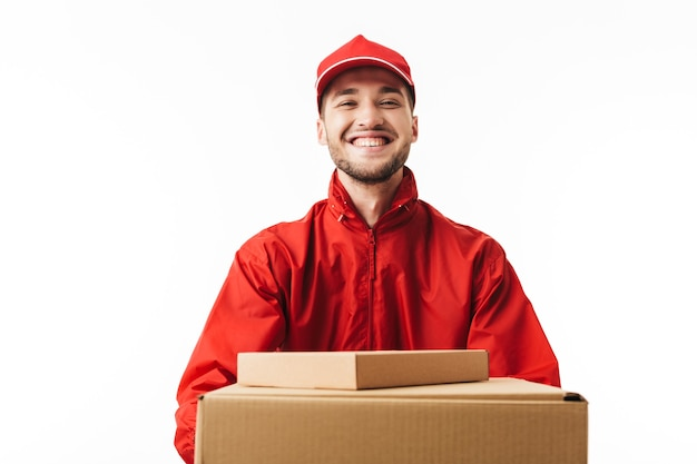 Young smiling delivery man in red cap and jacket holding boxes in hands joyfully