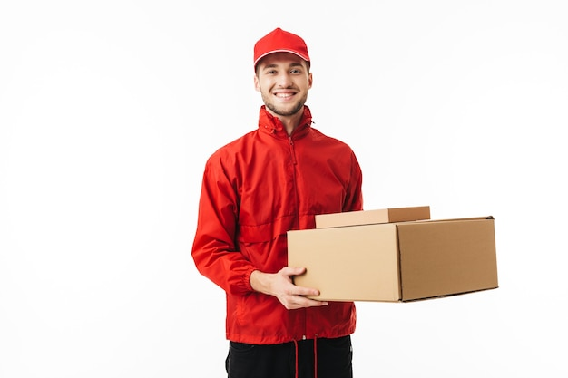 Young smiling delivery man in red cap and jacket holding boxes in hands while happily