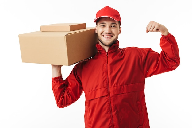 Young smiling delivery man in red cap and jacket holding parcel in hand happily showing force while