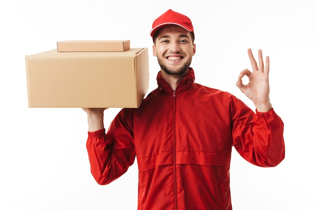 Young smiling delivery man in red cap and jacket holding parcel in hand happily showing ok gesture while
