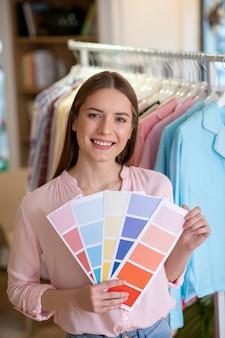 Молодая улыбающаяся дизайнерская девушка с цветовой гаммой в руках