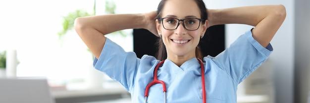 Молодой улыбающийся врач сидит за столом ноутбуком и держит голову в клинике