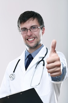 Young smiling doctor with thumbs up