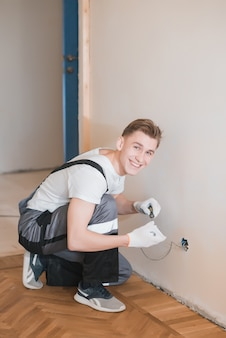 Young smiling electrician installing electrical socket on wall in house