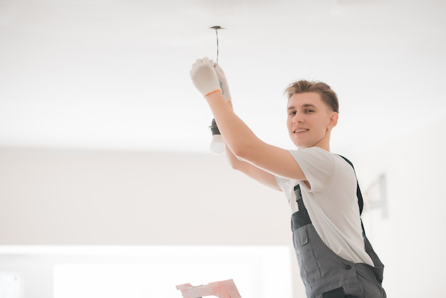 Young smiling electrician with a screwdriver repairing a ceiling lamp indoors. space for text