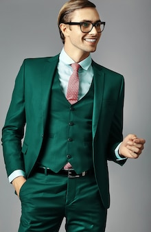 Young smiling elegant handsome  businessman male model in a suit and fashionable glasses,