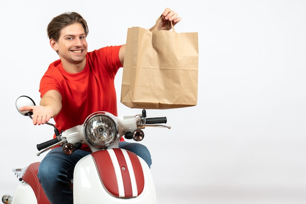 Young smiling emotional courier guy in red uniform sitting on scooter giving paper bag on white wall