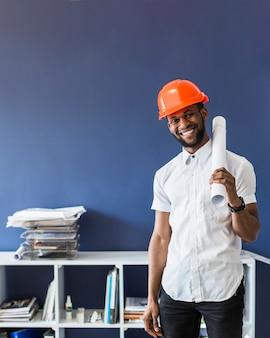Young smiling engineer wearing hardhat holding rolledup blueprint