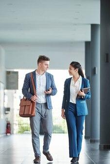 Молодые улыбающиеся предприниматели гуляют по коридору офиса и разговаривают о бизнес-проектах, над которыми работают