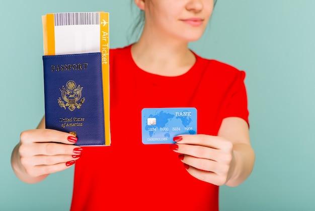 Молодая улыбающаяся возбужденная студентка с паспортом, посадочным талоном и кредитной картой