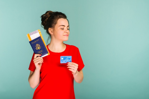 Young smiling excited woman student holding passport boarding pass ticket and credit card isolated on blue space. air travel flight