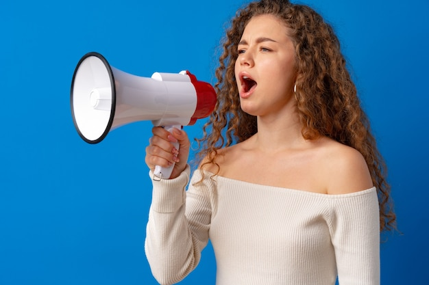 Young smiling expressive caucasian woman shout in megaphone against blue background