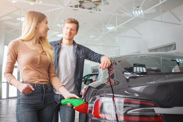 ショールームで最初の電気自動車を買って笑顔の家族カップル。夫を見ながら、電源ケーブルを差し込んだエコロジーハイブリッド車を充電する魅力的な女性のクローズアップ。